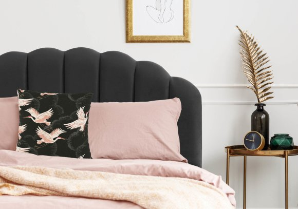 Framed sketch hanging above bed with dirty pink bedding and black cushion with golden pattern